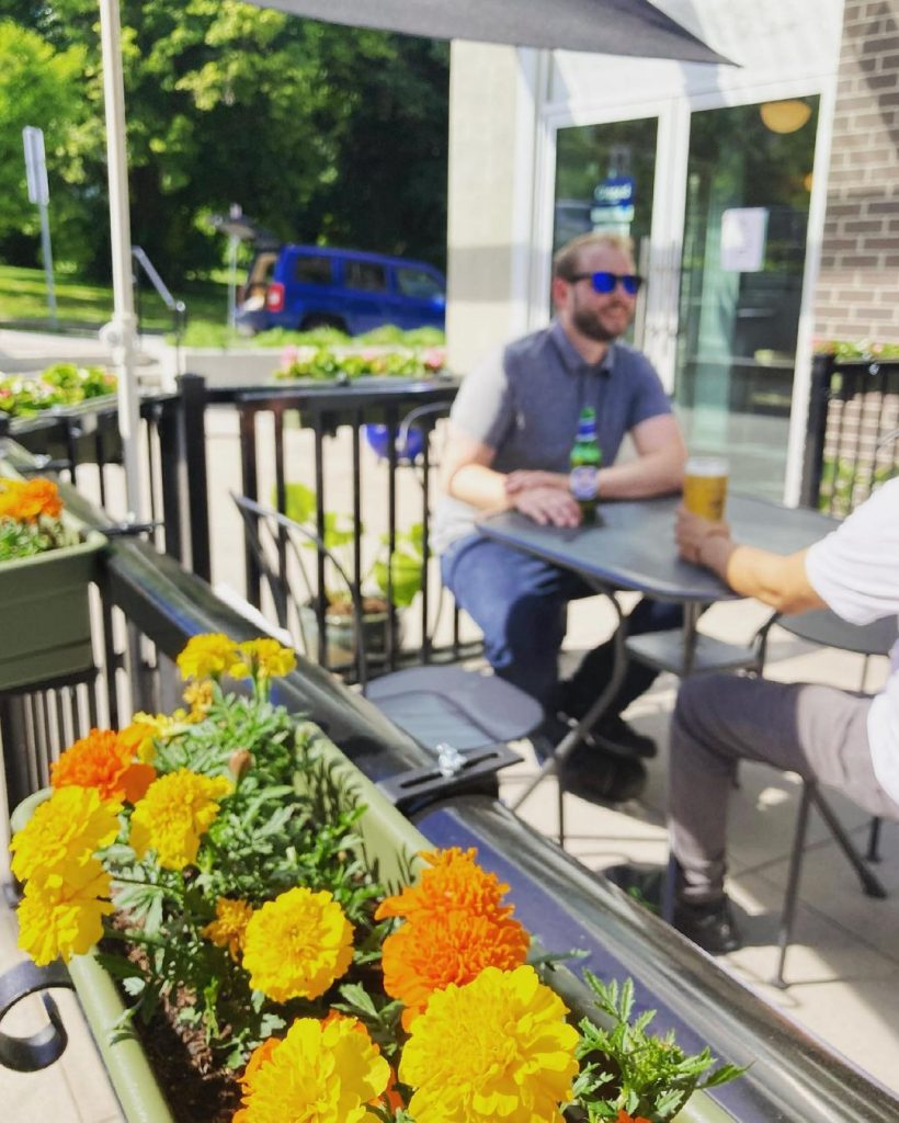 People eating on a patio with flowers