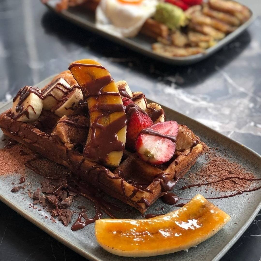 Assorted breakfast dishes including waffle topped with fruit and chocolate drizzle on a dark table