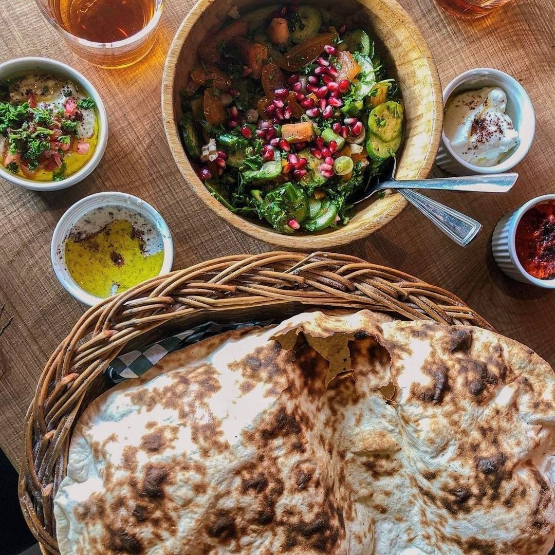 A colorful salad, golden flatbread and various dipping sauces on a wooden table.