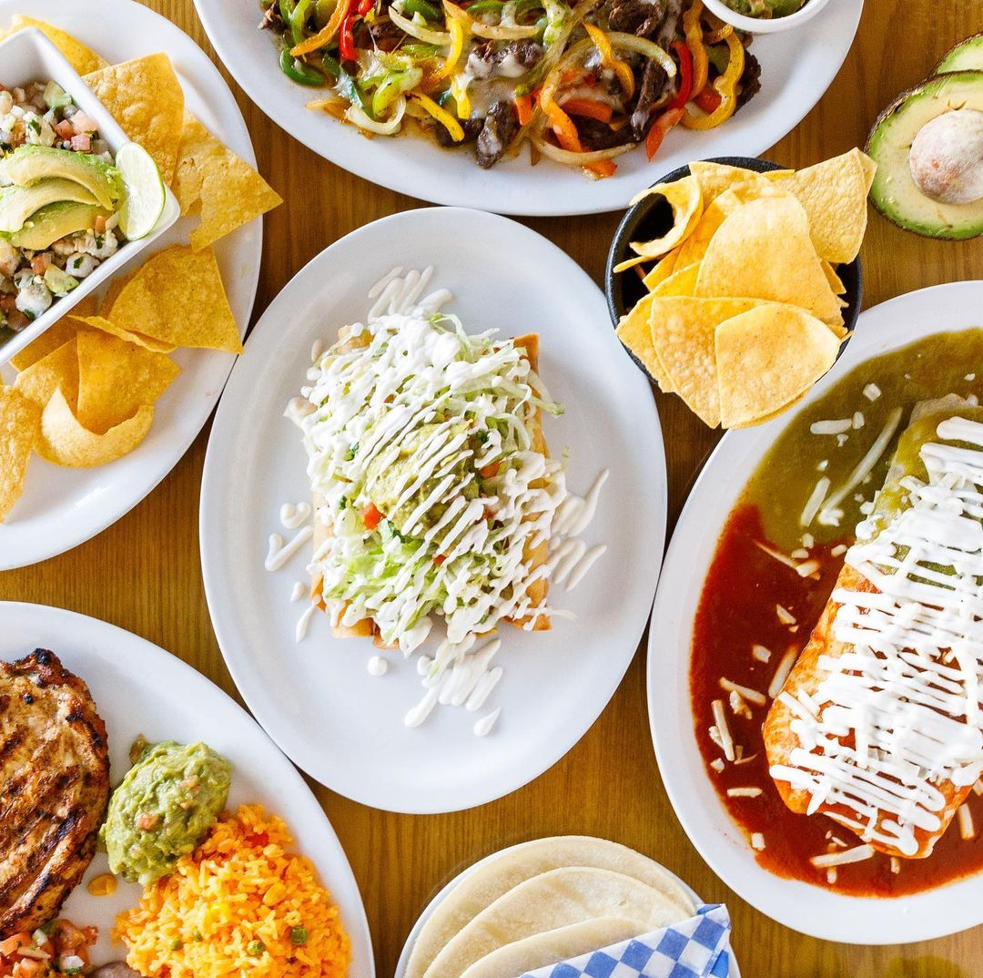 An assortment of Mexican dishes including burritos, tacos, and nachos.