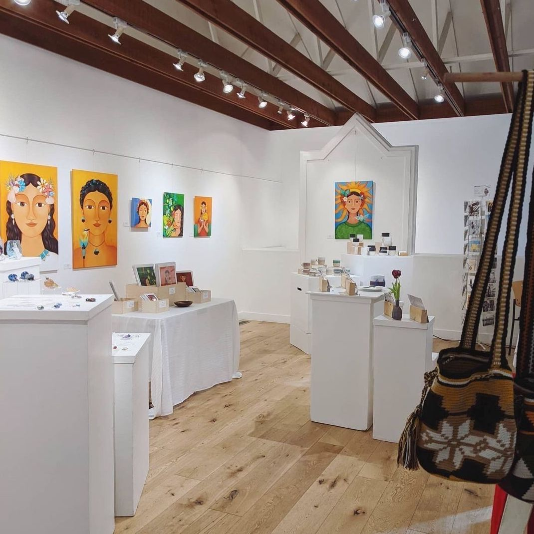 Paintings and other locally made goods on display in a gallery with white walls.