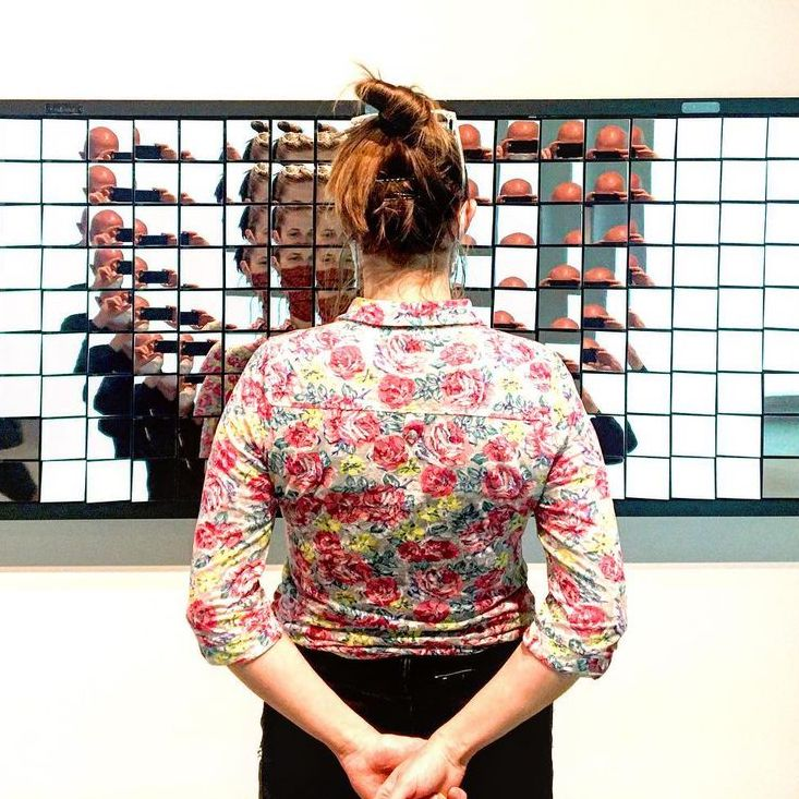 Woman standing in front of mirrored art piece.