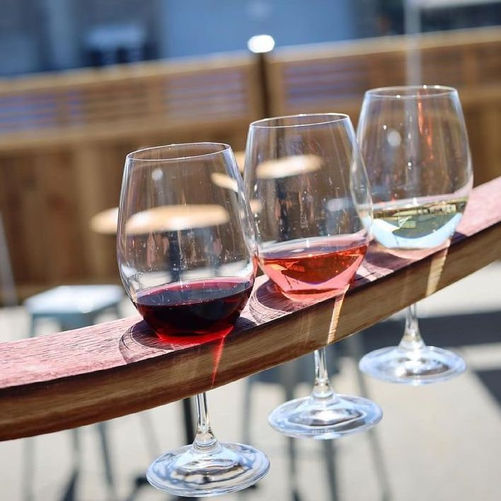 A glass of red wine, rosé, and white wine served as a flight