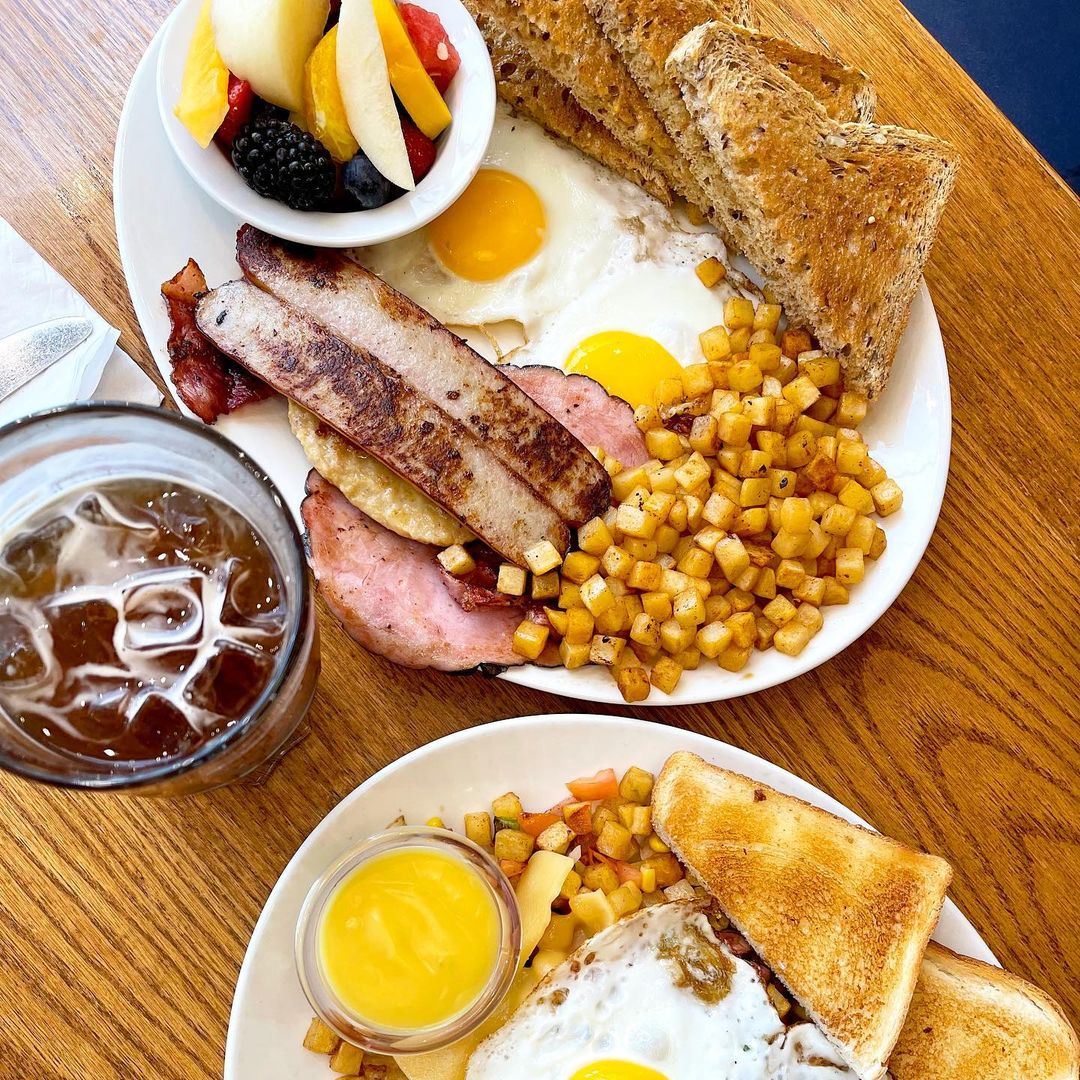 Assorted breakfast platters with fried eggs, toast, hasbrowns and sausages on a wooden table.