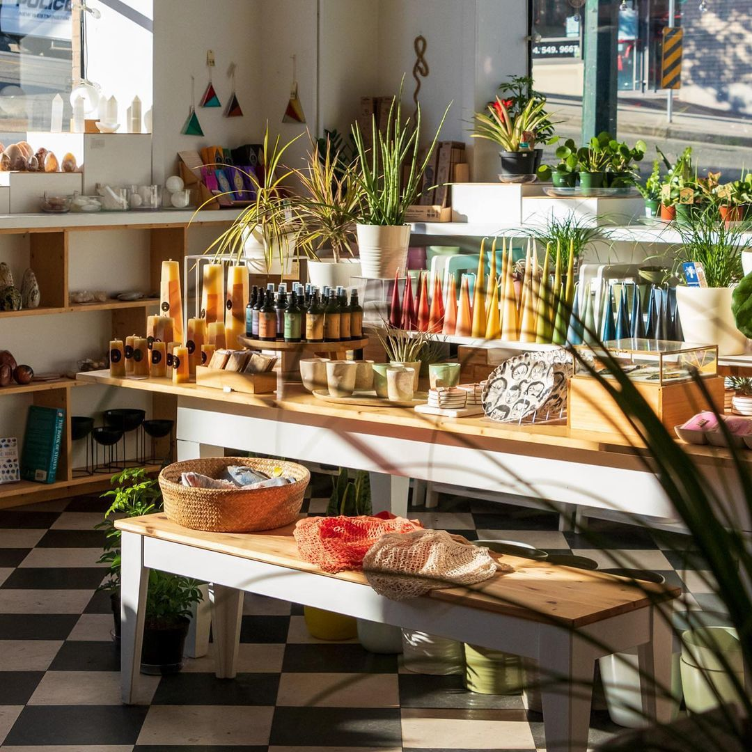 Locally made good, candles and plants on a sunlit table.