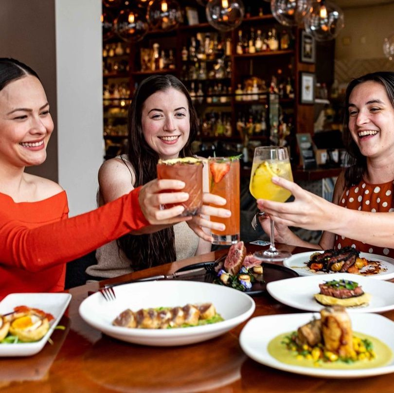 Three people toasting over a table of food.