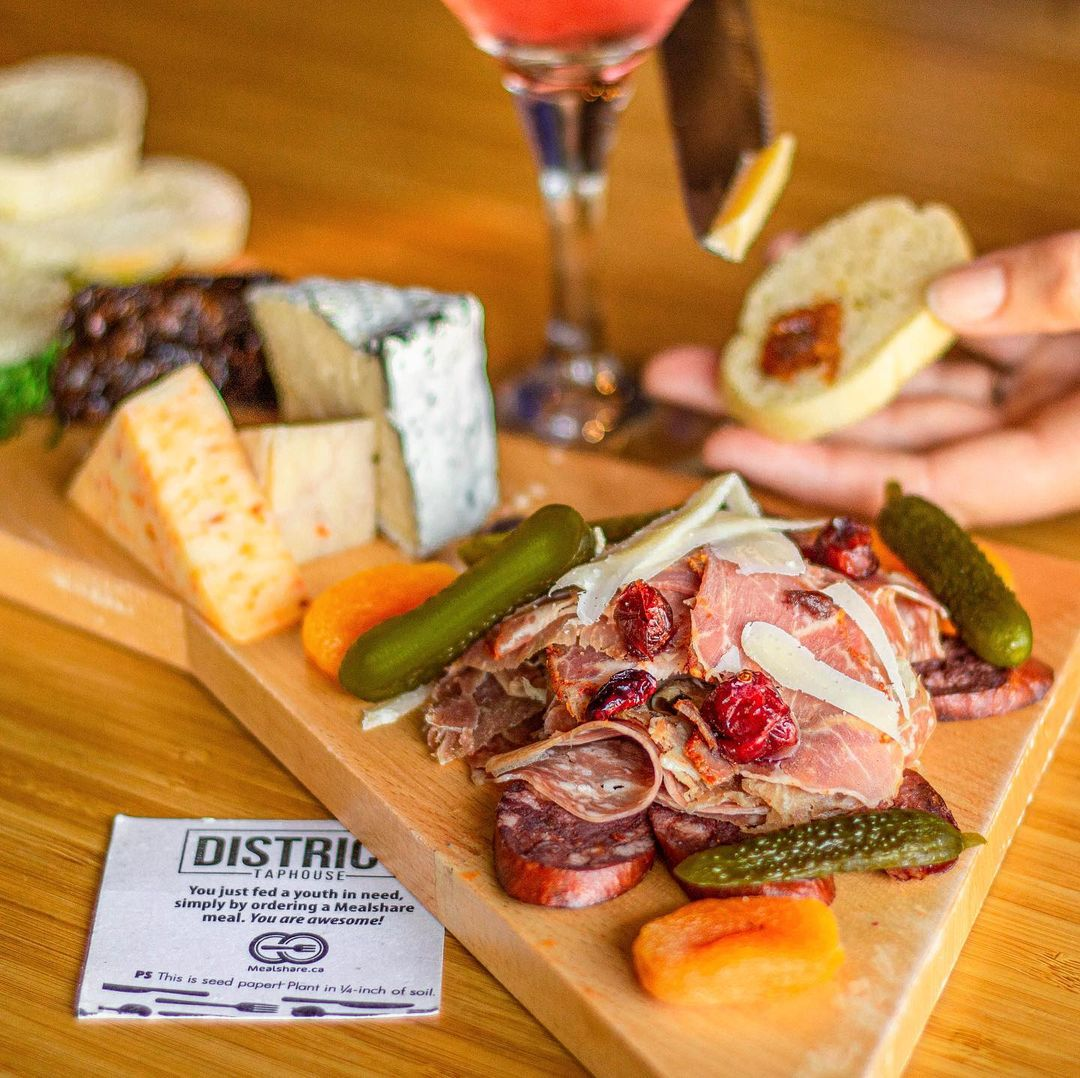 A charcuterie board with assorted cheese, meats, pickles and dried apricots.
