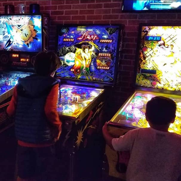 Kids playing brightly colored retro arcade games in a dark room.