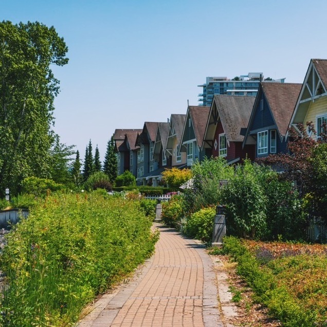 Colorful houses in a row along a walkway lined with bushes and flowers.